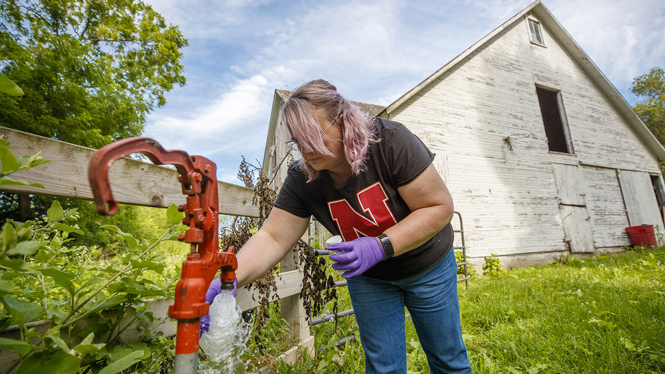 Jodi Sangster, a post-doc civil engineer specializing in environmental engineering, takes a water sample from a well spigot.