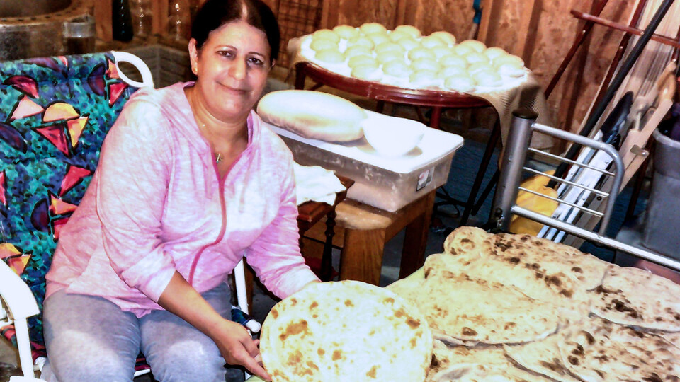 A Yazidi woman shows off a large batch of naan, a round, flat, leavened bread.