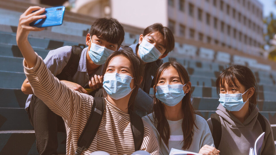 Asian students wearing masks taking a selfie with a phone