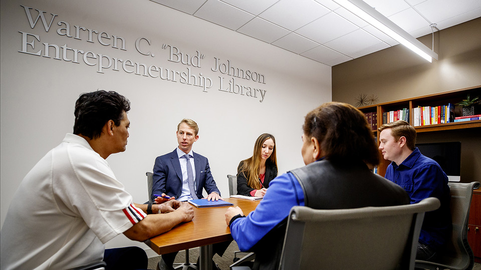 Third-year law students Brig Jensen and Nichole Sklare work with immigration clients in the University of Nebraska College of Law. Pictured to the right is second-year law student Eric Davis, who sat in to translate.