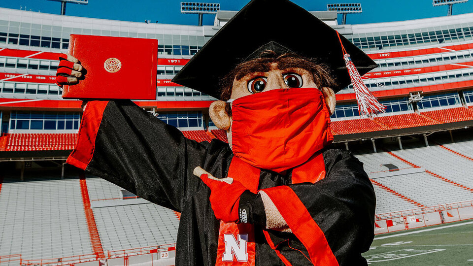 Herbie Husker wearing a mask in a graduation cap and gown pointing to a diploma
