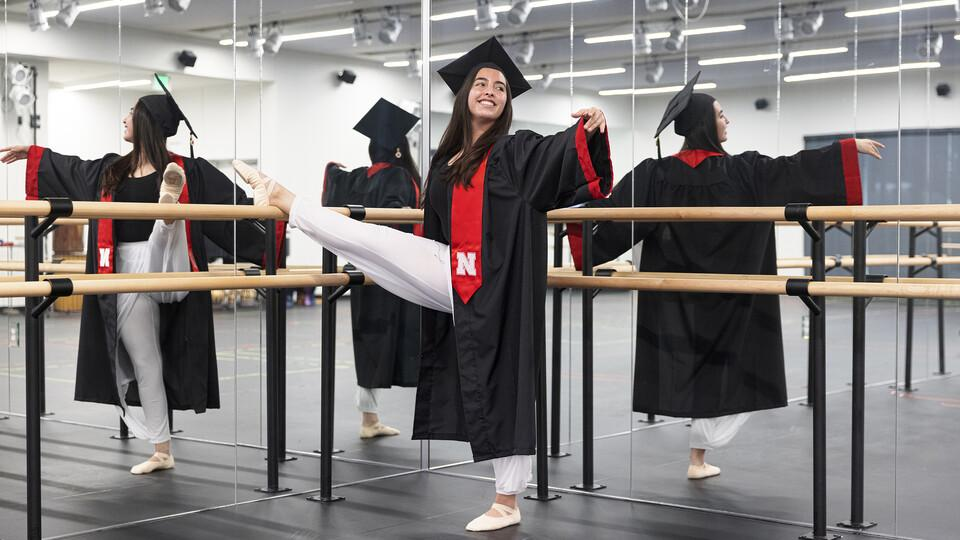 Anamaria Guzman Cardenas in a mirrored dance studio wearing her UNL cap and gown